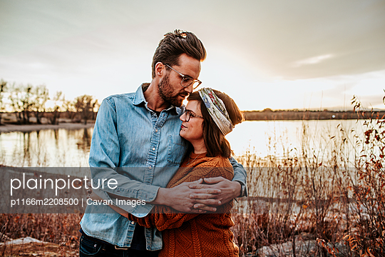 Hip young couple hugging near a lake on a warm autumn evening - p1166m2208500 by Cavan Images