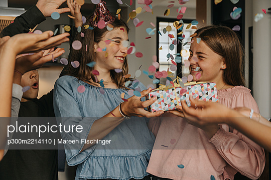 Friends throwing confetti on teenager giving gift to birthday girl in party - p300m2214110 by Mareen Fischinger