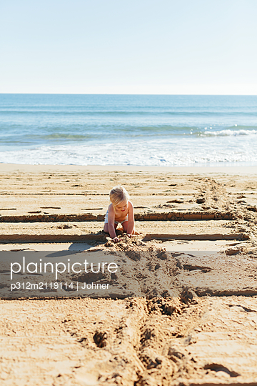 Girl playing on beach - p312m2119114 by Johner