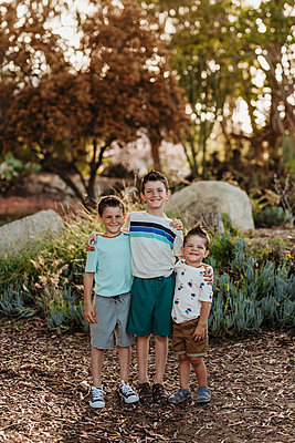 Portrait of three brothers smiling at camera in cactus garden - p1166m2136607 by Cavan Images