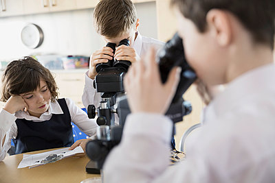 Elementary students using microscopes in science classroom - p1192m1024052f by Hero Images
