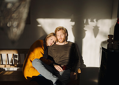 Relaxed couple sitting on bench in sunlight at home - p300m2205515 by Kniel Synnatzschke