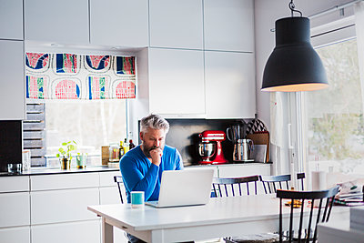 Man with laptop in kitchen - p352m1536607 by Calle Artmark