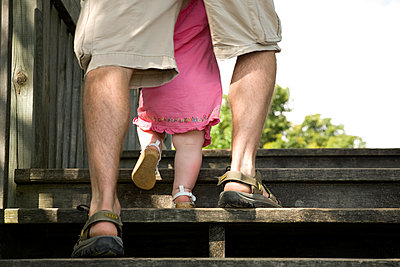 Dad Helping His Baby Daughter Climb Stairs - p442m883745 by Mary Ellen McQuay