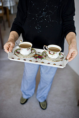 Elderly woman serves coffee in a pair of antique coffee mugs - p5350294 by Michelle Gibson