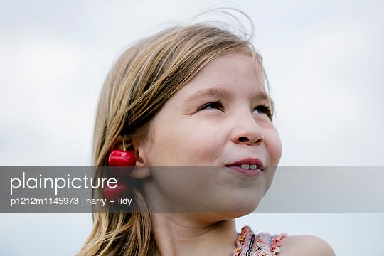 Mädchen mit Kirschohrringen vor Himmel - p1212m1145973 von harry + lidy