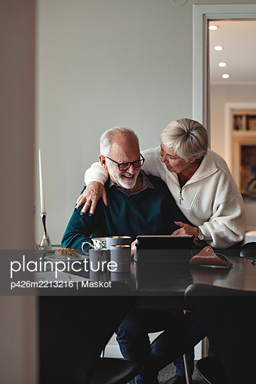 Smiling senior couple talking by dining table in living room - p426m2213216 by Maskot