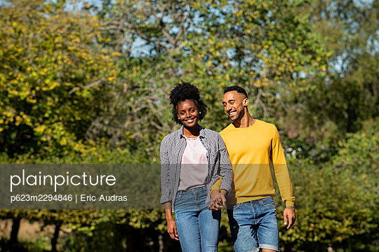 Smiling young couple with holding hands walking in public park - p623m2294846 by Eric Audras