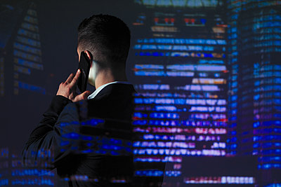 Double exposure businessman talking on smart phone against highrise lights at night - p1023m2135730 by Paul Bradbury