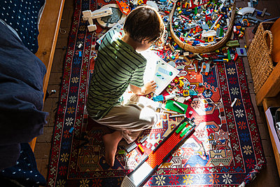 Boy sitting among toys on his bedroom floor in a patch of sunlight - p1100m2241952 by Mint Images