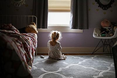 Rear view of girl sitting on carpet against window in bedroom - p1166m1554391 by Cavan Images