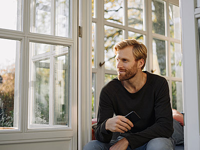 Man sitting in sunroom at home - p300m2166606 by Kniel Synnatzschke