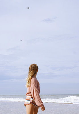 Teenage girl looking at helicopters flying over coastal beach - p300m2273687 by Arman Zhenikeyev