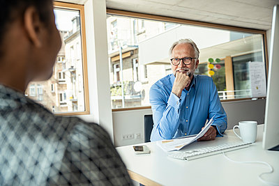 Smiling male professional with hand on chin discussing with female colleague in office - p300m2286850 by Uwe Umstätter
