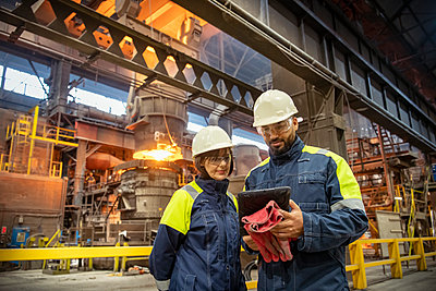 Male and female steelworkers using digital tablet during steel pour in steelworks - p429m2135017 by Monty Rakusen
