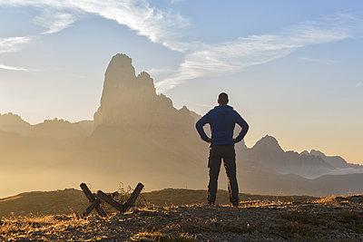 Europe, Italy, Veneto, Belluno, Cadore, Auronzo.  A man near the trenches of World War I on Monte Piana admires the Tre Cime di Lavaredo at sunrise - p651m2006683 by ClickAlps