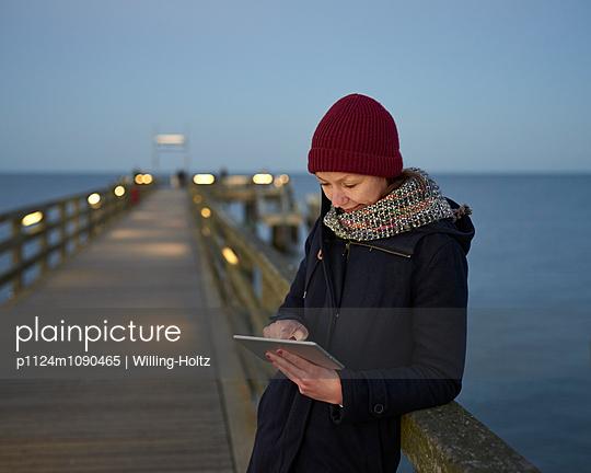 Frau mit Ipad auf Seebrücke - p1124m1090465 von Willing-Holtz