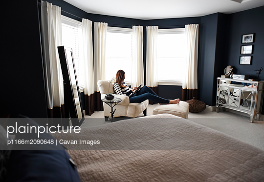 Woman sitting in chair on tablet in front of windows in a bedroom. - p1166m2090648 by Cavan Images