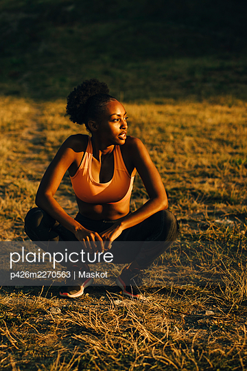 Sportswoman contemplating while crouching on land during sunset - p426m2270563 by Maskot
