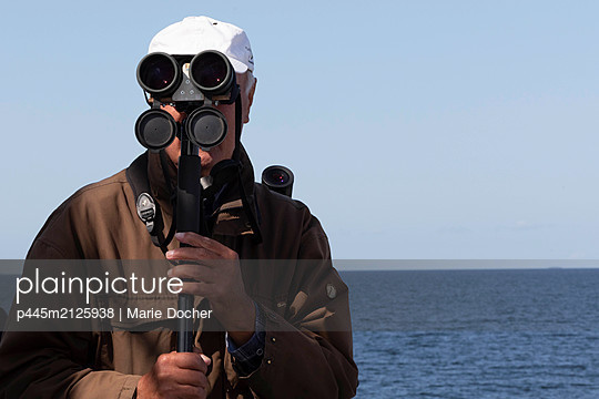 Man with binoculars - p445m2125938 by Marie Docher