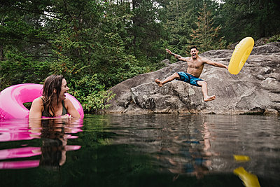 Playful young man with inflatable ring jumping into remote lake, Squamish, British Columbia, Canada - p1023m2066794 by Jarusha Brown