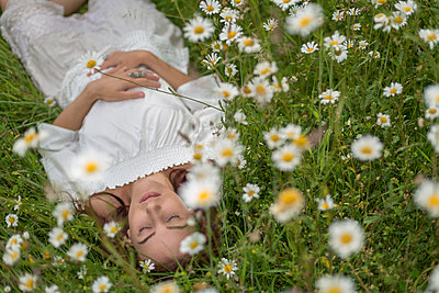 Young woman lying on her back in a field of marguerites - p1433m1585139 by Wolf Kettler