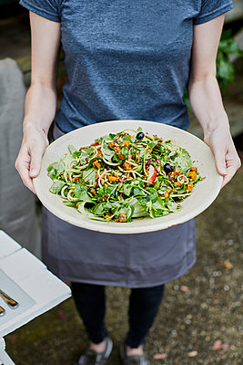 Woman serving mixed salad - p1612m2223536 by Heidi Coppock-Beard