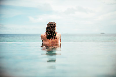 Rear view of woman relaxing in infinity pool, Maguhdhuvaa Island, Gaafu Dhaalu Atoll, Maldives - p300m2166309 by Daniel Waschnig Photography