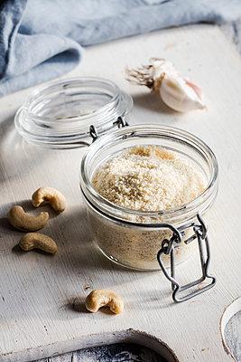 Cutting board with cashews and jar of shredded vegan Parmesan cheese - p300m2251161 by Eva Gruendemann
