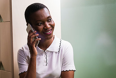 Smiling businesswoman talking on mobile phone at creative office - p300m2276223 by NOVELLIMAGE