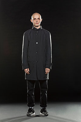 Full length portrait of serious bald man standing against black background - p301m1130788f by Vladimir Godnik