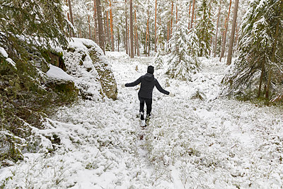Mature woman walking through snowy forest - p352m2120017 by Åke Nyqvist