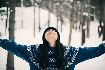 Happy woman standing with arms raised on snowy field during winter - p426m1588663 by Maskot