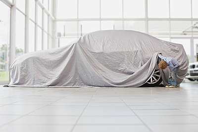 Boy peeking under cloth on car - p42915729f by Zero Creatives