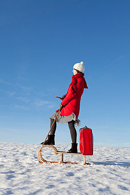 Woman standing on a sleigh with a suitcase - p4541197 by Lubitz + Dorner