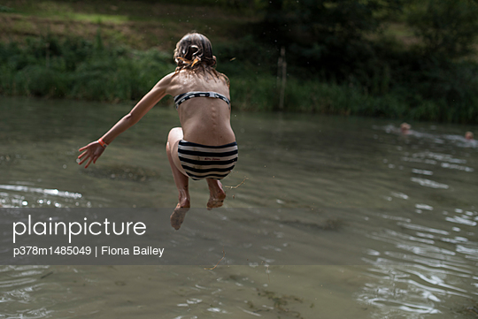 Girl jumping into water - p378m1485049 by Fiona Bailey