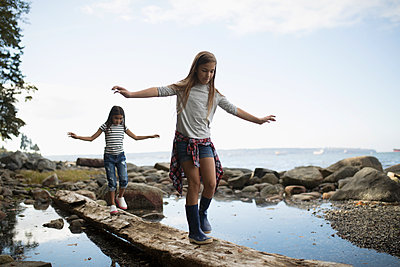 Girl friends walking, balancing on fallen log over water - p1192m1511819 by Hero Images