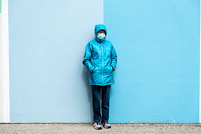 Woman wearing a blue jacket and mask - p1614m2211840 by James Godman