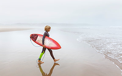 Spain, Aviles, young surfer walking towards the water - p300m2069823 by Marco Govel
