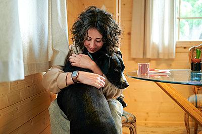 Smiling woman embracing dog at home - p300m2282284 by Kiko Jimenez