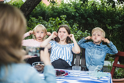Woman photographing children while making faces at dining table in garden party - p426m2135598 by Maskot