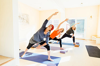 Three women practicing extended side angle lunge, (parsvakonasana) yoga pose in yoga studio - p429m1578387 by Ashley Corbin-Teich