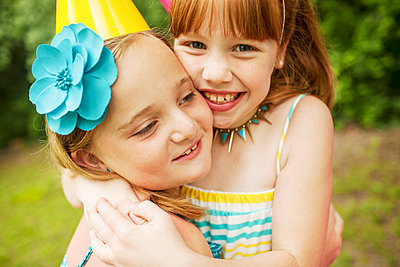 Girls hugging at birthday party outdoors - p555m1409063 by Shestock