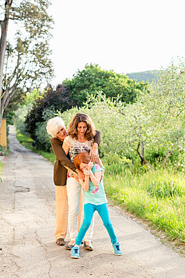 Girl on rural road with mother and grandmother - p924m2074530 by Innocenti