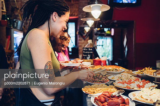 Happy friends taking food from buffet in a restaurant - p300m2202871 by Eugenio Marongiu