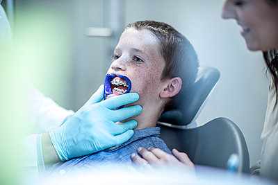 Boy with mother in dental surgery receiving orthodontic treatment - p300m1189618 by zerocreatives