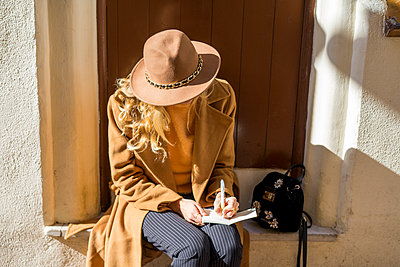 Fashionable young woman sitting at house entrance writing in notebook - p300m1562955 by VITTA GALLERY