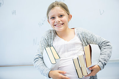 Portrait of happy schoolgirl carrying books in class - p300m2005281 von Fotoagentur WESTEND61