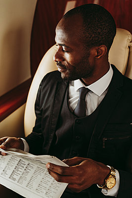 Businessman with newspaper looking away in private jet - p300m2256409 by OneInchPunch