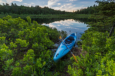 A kayak on the shore of Round Pond in Barrington, New Hampshire. - p343m1443423 by Jerry Monkman